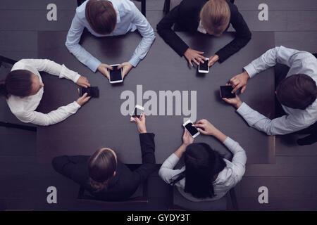 Les gens d'affaires avec les smartphones assis autour de la table, vue du dessus Banque D'Images