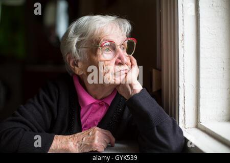 Femme âgée dans les verres pensivement en regardant par la fenêtre. Banque D'Images