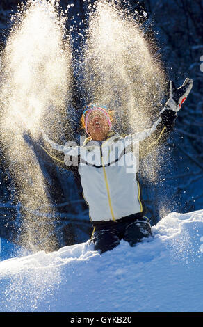 Woman throwing snow haut dans l'air, France Banque D'Images
