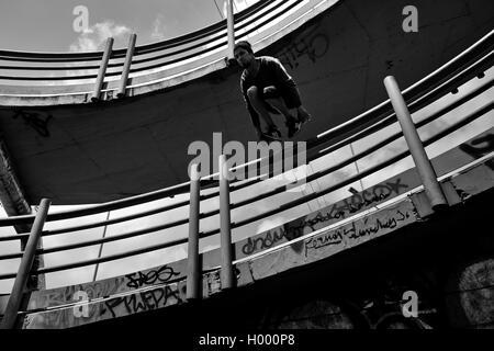 Steven Mantilla, un parkour runner de l'équipe de Tamashikaze, saute par-dessus le garde-corps passerelle à Bogotá, Banque D'Images