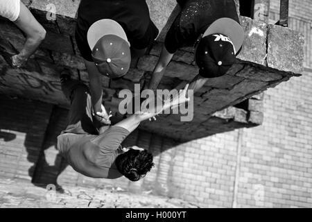 Un parkour runner, suspendu à ses copains' hands, grimpe sur le mur pendant une session de formation à Bogotá, Colombie. Banque D'Images