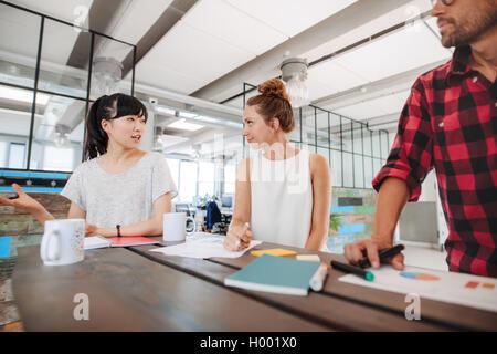 Groupe de jeunes lors d'une réunion de remue-méninges autour de table en bureau de démarrage. L'équipe diversifiée Banque D'Images