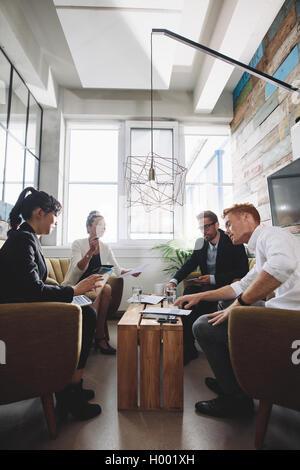 Groupe de personnes créatives assis ensemble et discuter de nouveau projet d'entreprise dans le bureau. Banque D'Images