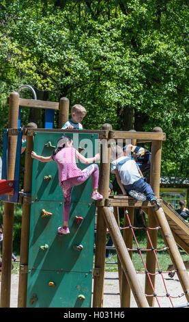 Une fille grimpe sur le mur d'escalade pour enfants au parc Banque D'Images