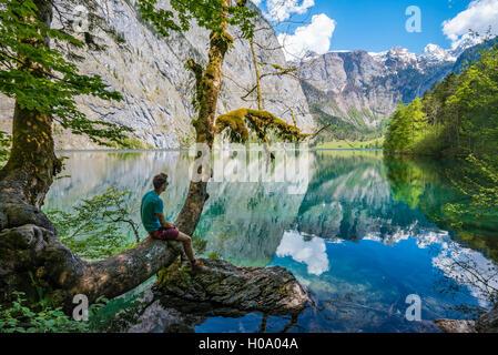 Jeune homme assis sur un arbre au-dessus de l'eau, à la réflexion, en distance, dans le lac Obersee, salet am Königssee