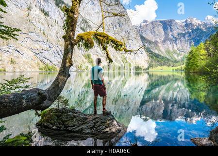 Jeune homme debout sur la pierre dans l'eau, à la réflexion, en distance, dans le lac Obersee, salet am Königssee