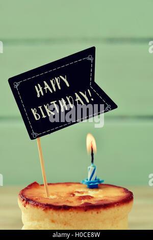 Libre d'un cheesecake surmontée d'une pancarte en forme de drapeau noir avec le texte joyeux anniversaire écrit Banque D'Images