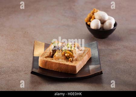 Toast aux champignons cuits fort sur la plaque en arrière-plan gris Banque D'Images