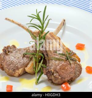 Escalope de porc rôti de côtes avec rosemarry et sauce tomate sur plateau blanc