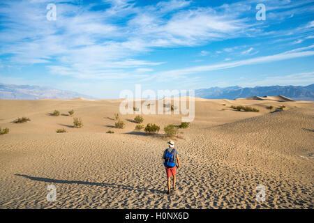 Jeune homme randonnée sur les dunes de sable, touristiques, de Mesquite Flat dunes de sable, contreforts de l'Amargosa Range derrière, la vallée de la mort