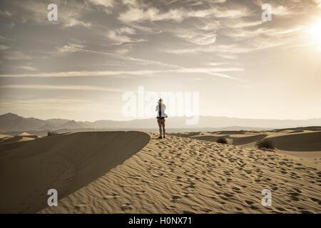 Young man photographing sand dunes, touristiques, de Mesquite Flat dunes de sable, contreforts de l'Amargosa Range derrière, la vallée de la mort