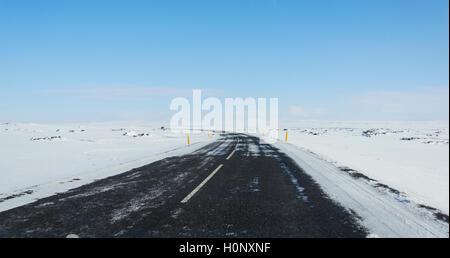 Route à travers des paysages enneigés, ring road, route nationale 1 ou Hringvegur, île du nord de l'île,