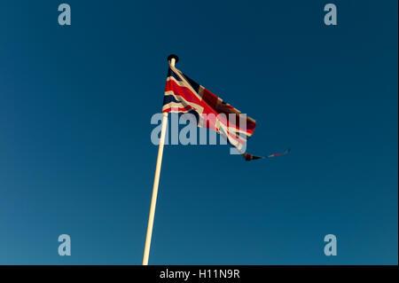 Tattered Union Jack flag against blue sky Banque D'Images