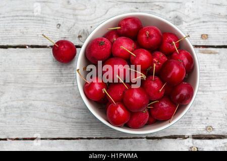 Les pommettes rouges mûres sur une table de pique-nique en bois. Banque D'Images