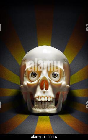 Effrayant crâne humain avec les yeux regardant fixement, sur un fond noir avec bandes jaunes
