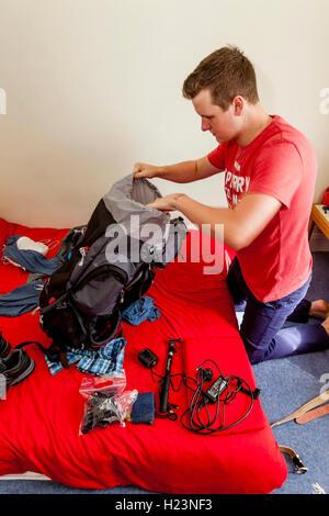 Un jeune homme Packs son sac à dos pour voyager, Sussex, UK Banque D'Images