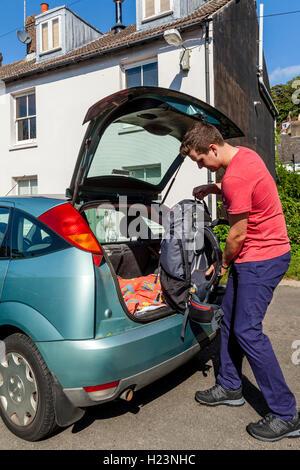 Un jeune homme met son sac à dos dans une voiture pour voyager, Sussex, UK Banque D'Images