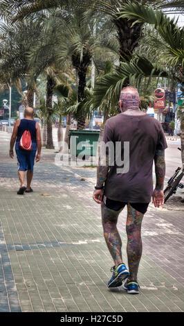 Fortement tattooed man créer une situation inquiétante à la suite d'une marchette. Banque D'Images