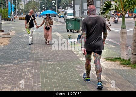 Fortement tattooed man créer une situation inquiétante avec approche de couple de personnes âgées. Banque D'Images