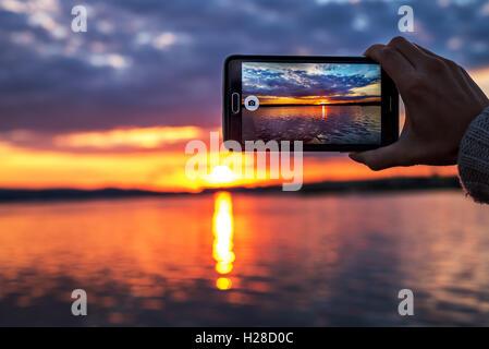 Femme hands holding mobile phone au coucher du soleil. Banque D'Images