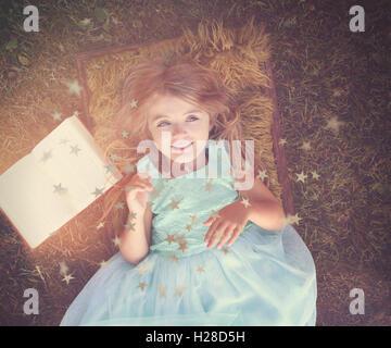 Une jolie fille est heureuse portant sur l'herbe à l'extérieur avec un livre d'histoires pour un mystère, l'imagination Banque D'Images