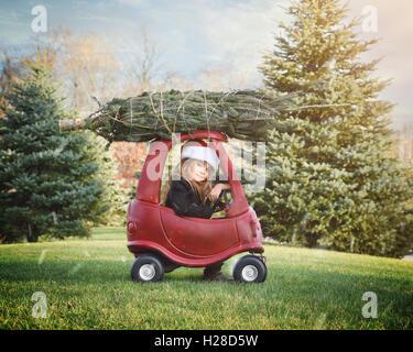 Une fille est d'avoir ramené un arbre de Noël sur le dessus d'un toit à l'extérieur dans la neige pour une maison Banque D'Images