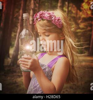 Une petite fée fille est dans les bois avec une bouteille magique pour une imagination ou fantaisie concept. Banque D'Images