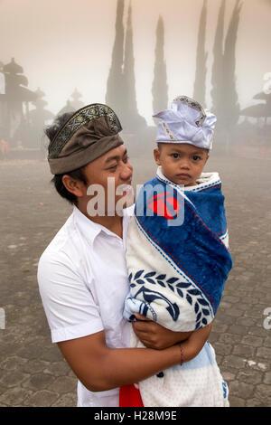 L'INDONÉSIE, Bali, Batur, Pura Ulun Danu Batur, homme portant chapeau udeng traditionnels exerçant son jeune fils Banque D'Images