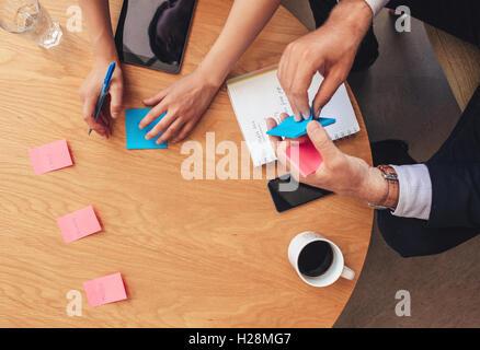 Vue de dessus deux personnes assis autour d'une table et d'écrire sur les post it. Remue-méninges avec des notes Banque D'Images