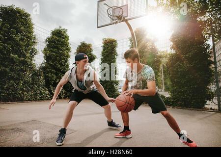 Amis adolescents jouer streetball les uns contre les autres et s'amuser. Deux jeunes hommes ayant un match de basket-ball extérieur sur cour