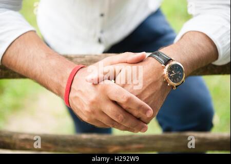 Mains homme adulte portant watch et bracelet leaning on wooden fence Banque D'Images