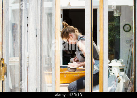 Une femme d'argile de potier sur un tour de potier dans son atelier.