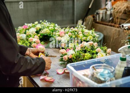 Fleuriste commercial. Une femme travaillant sur une décoration florale à un établi. Banque D'Images