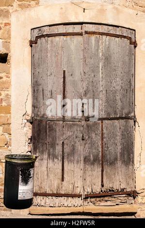 Ancienne porte fermée avec la rouille sur mur de pierre. À jeter? Corbeille à proximité. Banque D'Images