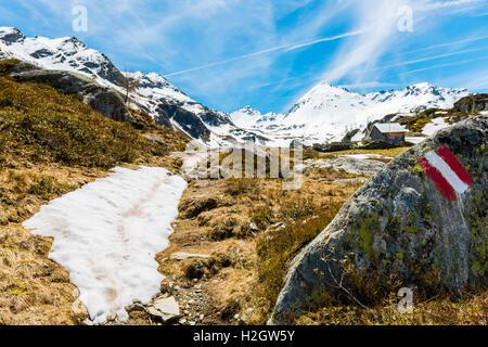 Signe rouge et blanc peint sur le sentier de randonnée de marquage rock, cabane en arrière-plan, les montagnes, Banque D'Images