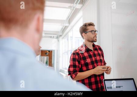 Businessman in casuals donnant présentation sur tableau blanc à ses collègues dans la salle de conférence. Banque D'Images
