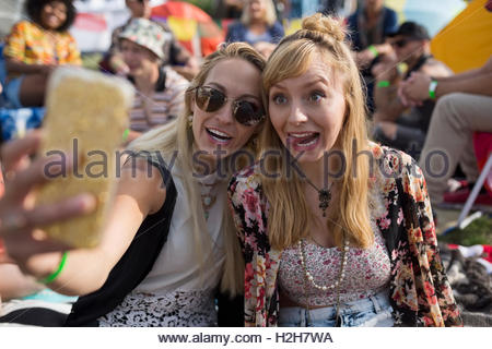 Les jeunes femmes espiègles making a face en tenant à selfies summer music festival camping Banque D'Images