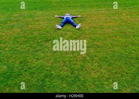 Fille blonde allongée sur une pelouse verte Banque D'Images