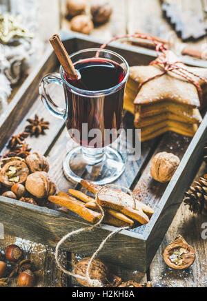 Verre de vin chaud en plateau en bois avec Noël gingerbread cookies, les noix, la cannelle, l'anis et des pommes Banque D'Images