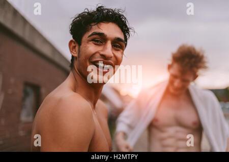 Portrait de beau jeune homme torse nu à la caméra en souriant et avec des amis en arrière-plan. Banque D'Images