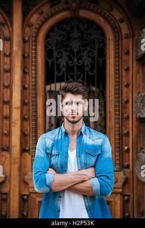 Beau jeune homme debout en face de la belle porte en bois, l'attente de quelqu'un à l'extérieur Banque D'Images