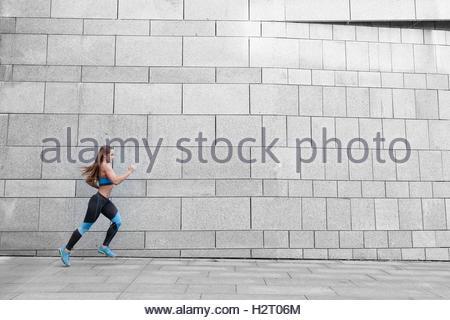 Athlète coureur s'exécutant sur fond gris. Entraînement jogging fitness femme. Concept de bien-être. Banque D'Images