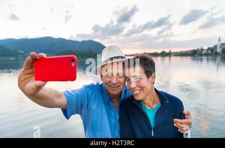 Man and Woman smiling, prendre des photos avec un téléphone mobile, Schliersee, selfies, Haute-Bavière, Bavière, Banque D'Images