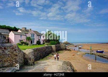 Un nouveau paysage de bord de mer de deux personnes se tenant la main à pied jusqu'à Bude Cornwall dans le port Banque D'Images