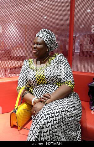 Femme en robe d'impression textile africaine gars visite jour Centre de cancérologie de l'hôpital à Southwark, Londres, Banque D'Images