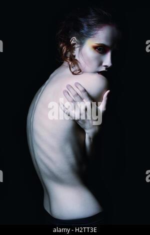Effrayant sombre portrait d'une jeune fille parmi l'obscurité Banque D'Images