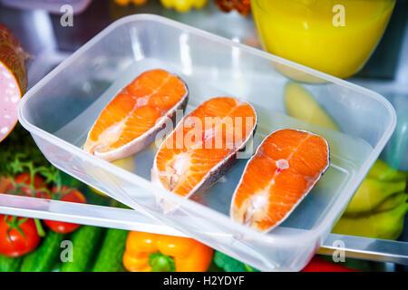Pavé de saumon cru dans le réfrigérateur ouvert Banque D'Images