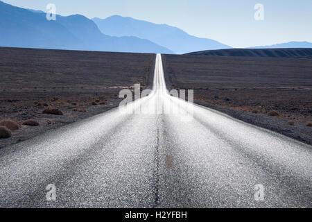 Route droite en direction de montagnes en horizon à Death Valley, Etats-Unis