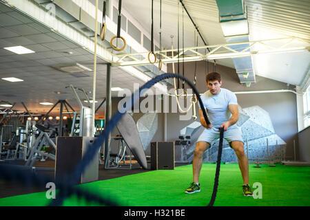 L'homme athlétique bataille avec la corde dans l'entraînement fonctionnel fitness gym Banque D'Images