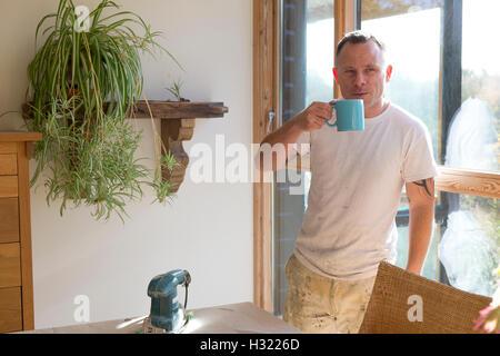 Menuisier bois ayant une pause du travail et prendre une tasse de thé au soleil Banque D'Images